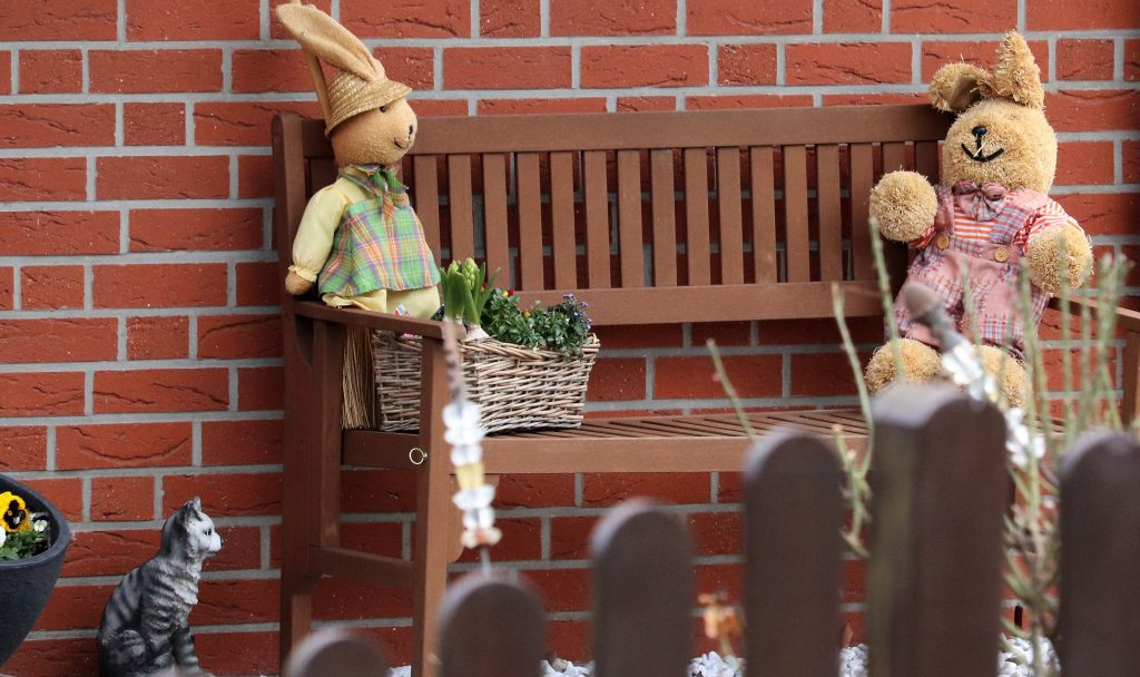 Zwei Stoffhasen auf einer Gartenbank mit Blumenkorb, nebenan eine Katze
