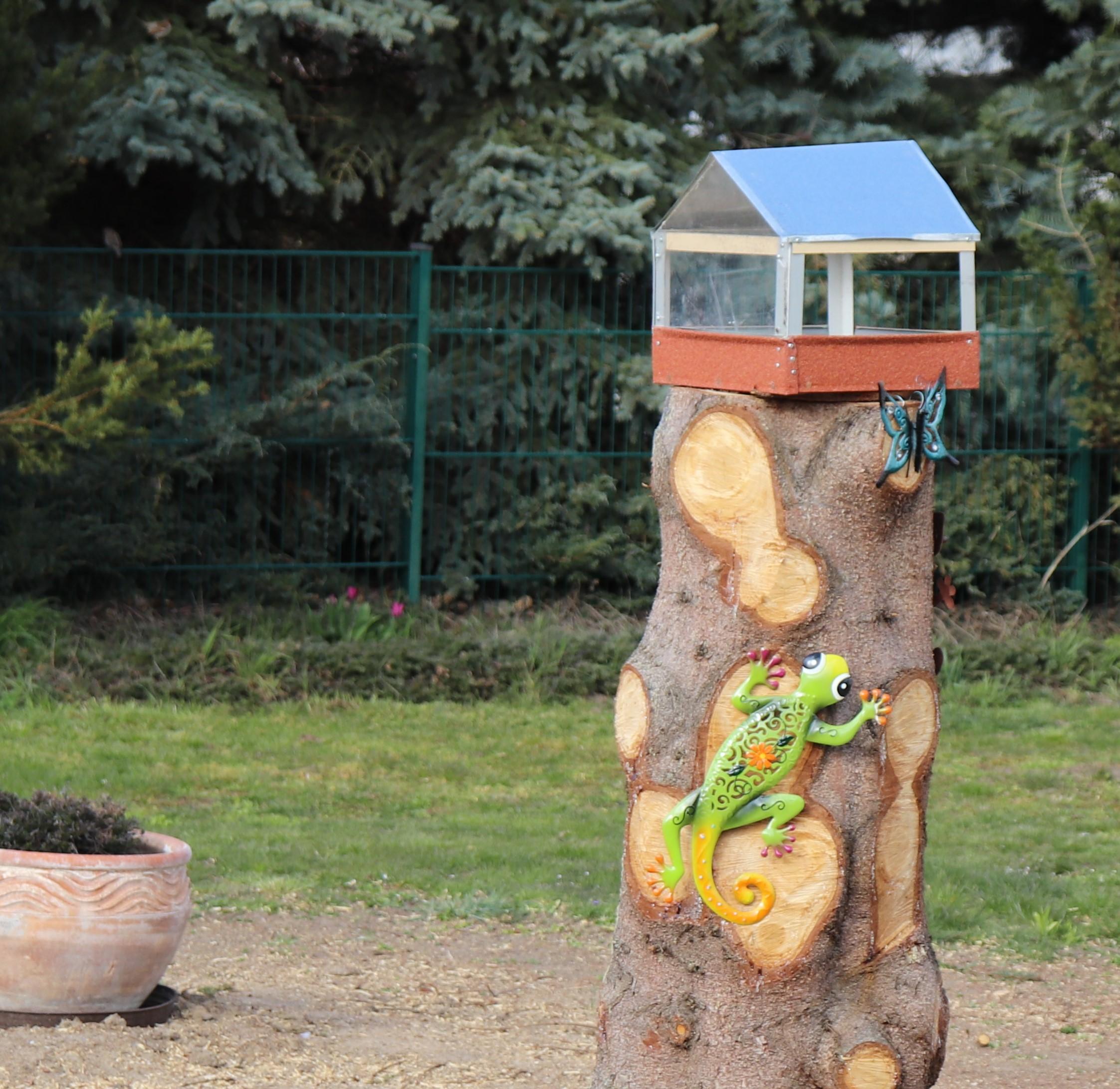 Vogelhäuschen auf Baumstamm mit Eidechse